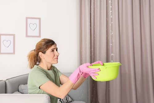Lady with bucket under Leaking Roof